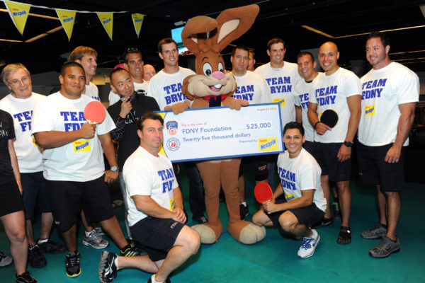 Gold medalists and champion tennis players Bob, second right of bunny, and Mike Bryan, left of bunny, present members of the FDNY with a check for $25,000 to the FDNY Foundation after the Nesquik FDNY Foundation Charity Ping Pong tournament at SPiN Galactic in New York, Thursday, Aug. 23, 2012.  The Bryan Brothers took on FDNYÕs ace ping pong players to pay tribute to and support the FDNY.  (Diane Bondareff/Invision for Nesquik/AP Images)
